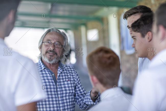 Teacher talking to students on school corridor