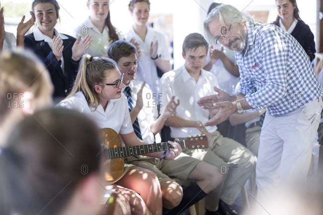 Teacher and students having music lessons outside