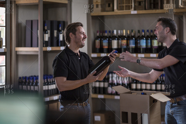 Two men with wine bottle in shop