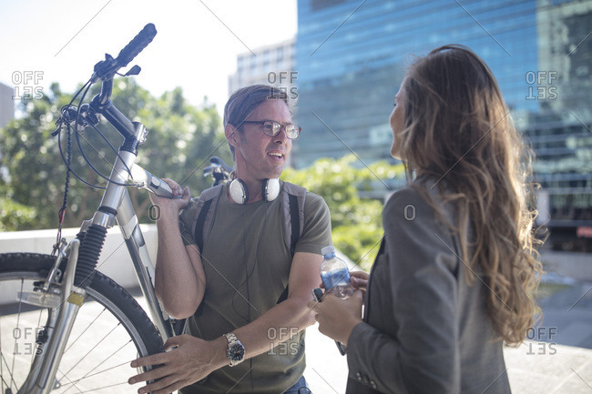 Young woman talking to young man- carrying bicycle on his shoulder