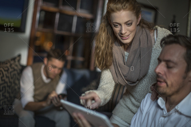 Woman talking to man using tablet