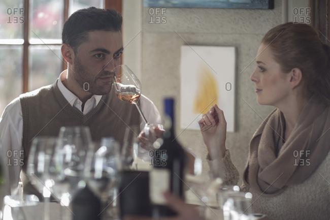 Couple tasting wine together at restaurant