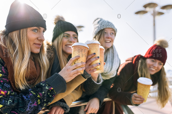 Four friends toasting with coffee to go in winter