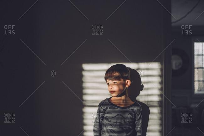 Boy standing against wall in window light