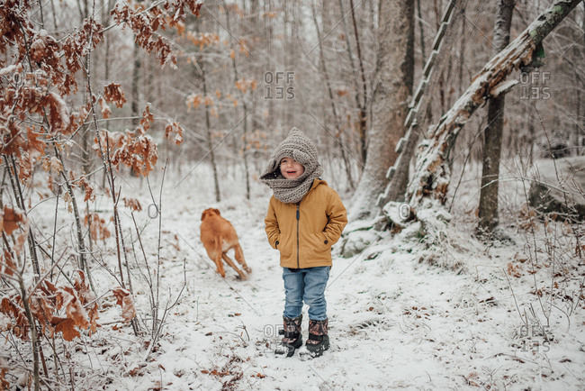 Toddler boy and dog in snowy forest