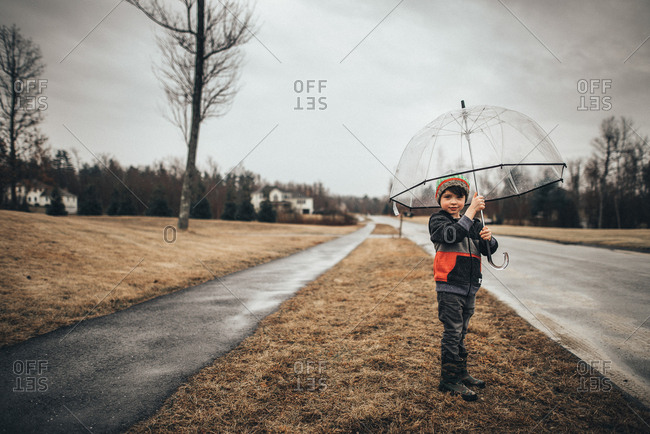 Young boy outside with clear umbrella