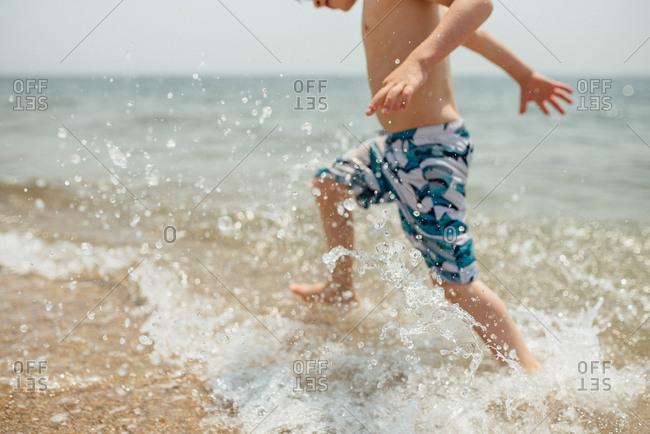 Little boy splashing in the waves at a beach