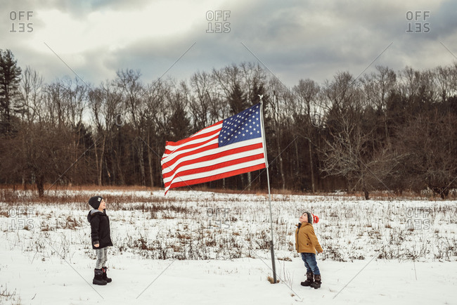 Boys standing by an American flag in the snow