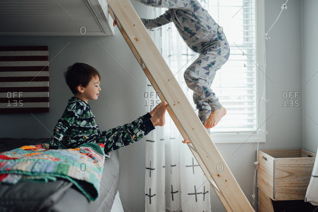 Boy on bottom bed while brother climbs the ladder to the top bunk