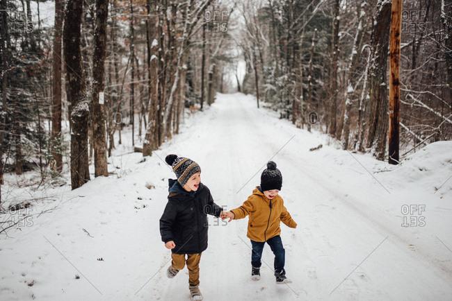 Two boys running on a snowy path