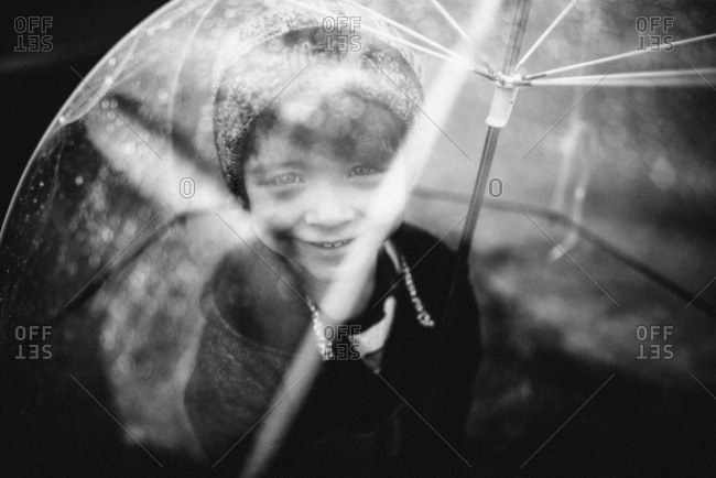 Young boy outside with clear umbrella in black and white