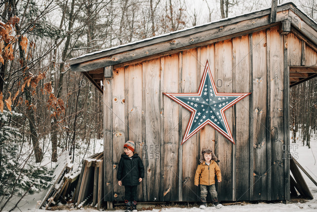 Two brothers standing by a woodshed in winter