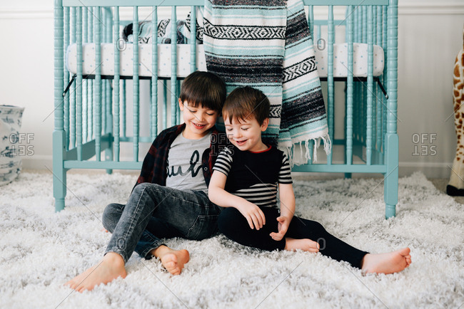 Brothers sitting on bedroom floor by crib