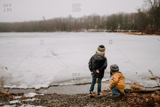 Brothers throwing rocks into icy lake