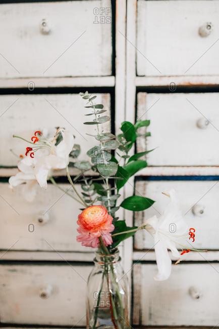 Floral arrangement in vase by white dresser