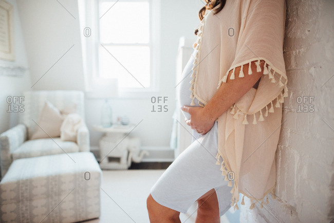 Woman leaning on wall holding pregnant belly