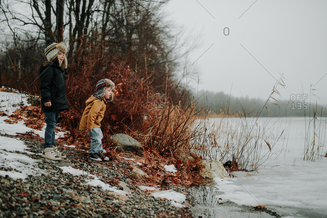 Side view of boys throwing rocks into icy lake