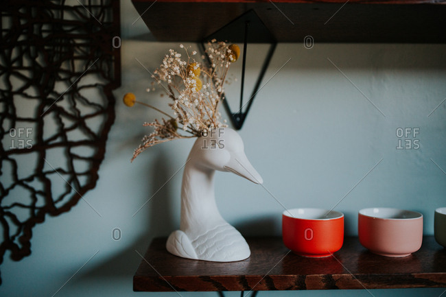 Duck figurine and ceramic bowls on a shelf