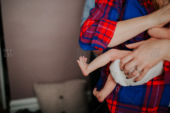 Woman in a plaid shirt holding her newborn child