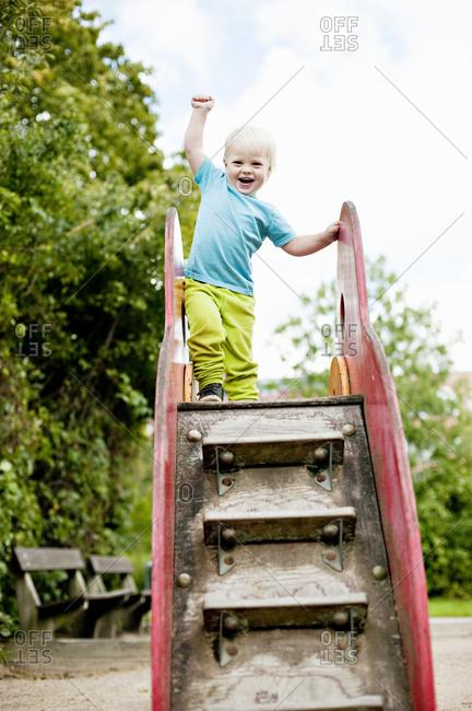 Smiling boy standing on slide