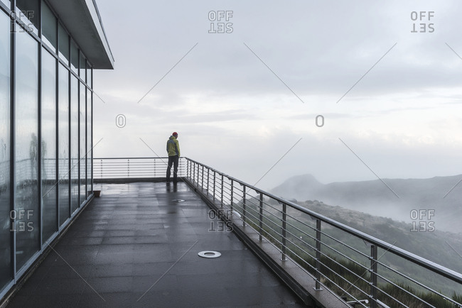 Man standing on terrace and looking at view