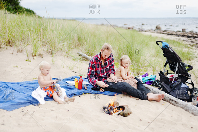 Father with two children relaxing on beach