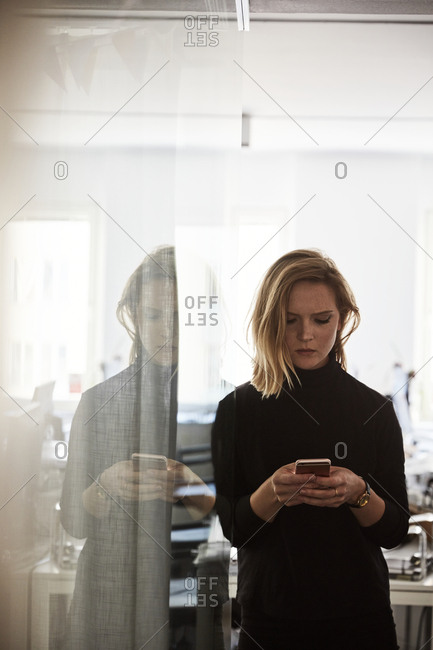 Woman in office with mobile phone
