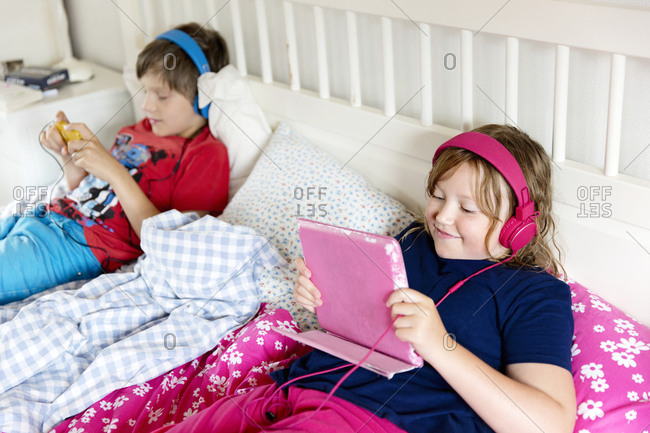 Brother and sister using wireless devices
