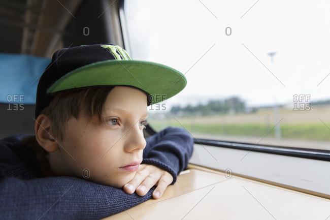 Boy in train looking through window
