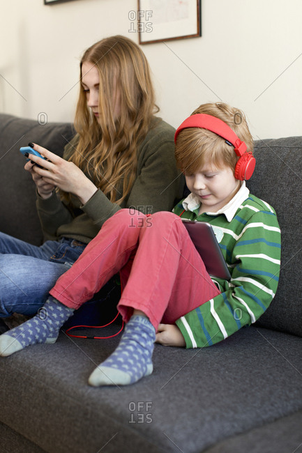 Boy and mother on sofa using wireless devices