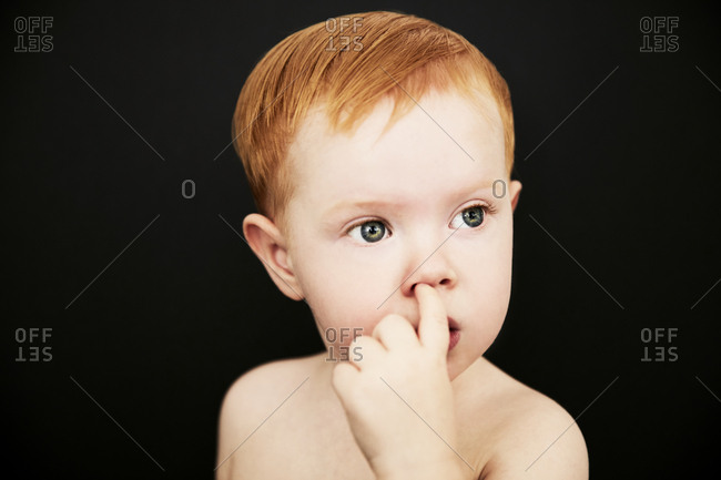 Portrait of toddler picking his nose