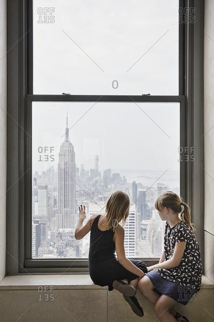 Girls looking through window at skyscrapers