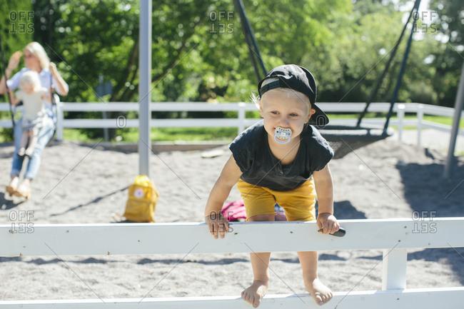 Toddler climbing fence