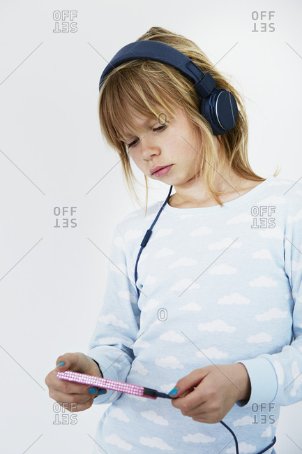 Girl with headphones holding cell phone