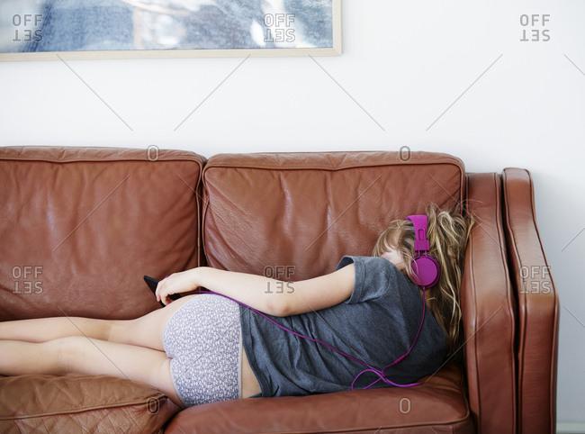 Girl with headphones lying on sofa