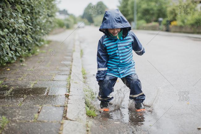 Boy splashing in puddle