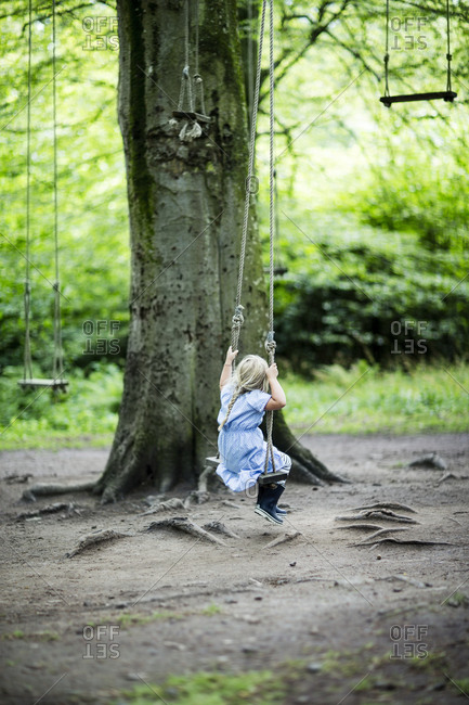 Small girl swinging in forest