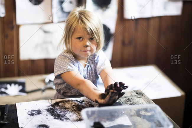 Small girl painting with black paint
