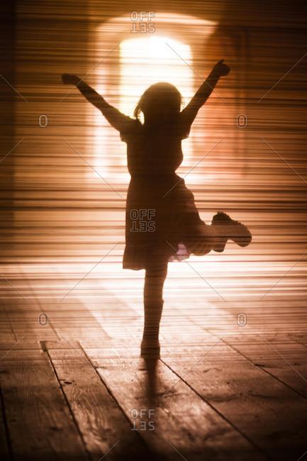Silhouette of girl dancing on wooden floor