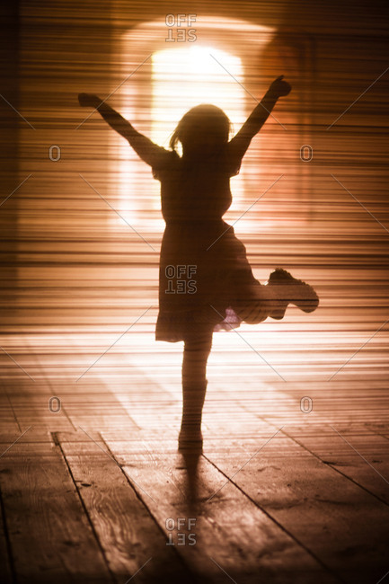 Silhouette of girl dancing on wooden floor