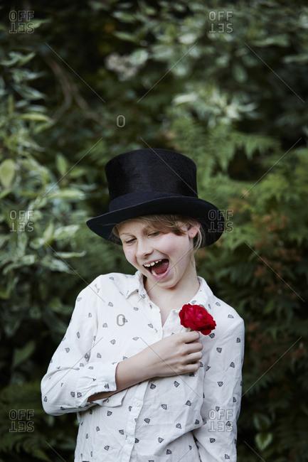 Girl in black hat, holding red rose