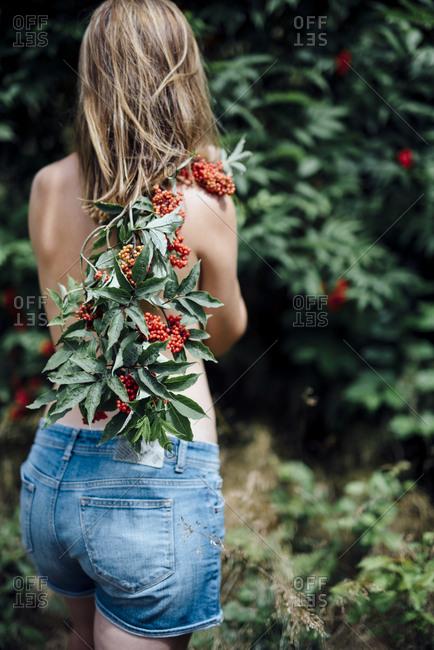 Teenage girl holding rowan tree branch