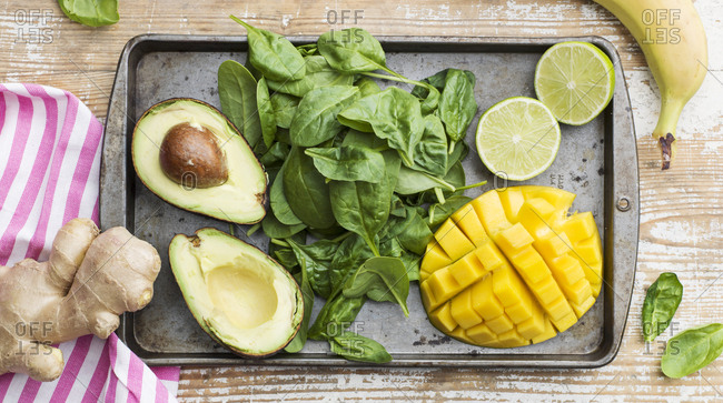 Spinach, avocado and pineapple on baking tray