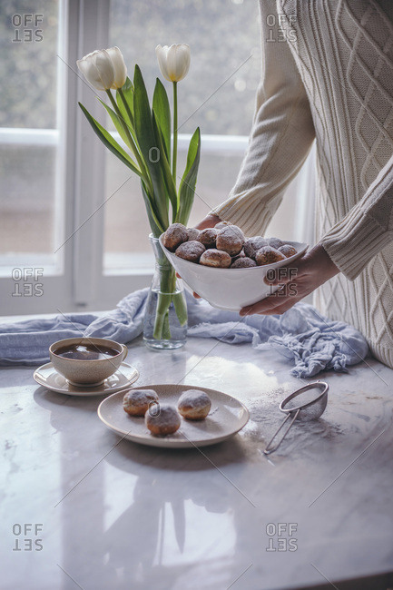 Woman holding a white bowl with Castagnole, Italian sweet fritters