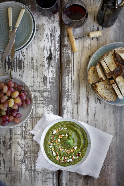 Gorgonzola Hazelnut Cilantro Pesto served in a ceramic bowl with crostini, grapes and wine.