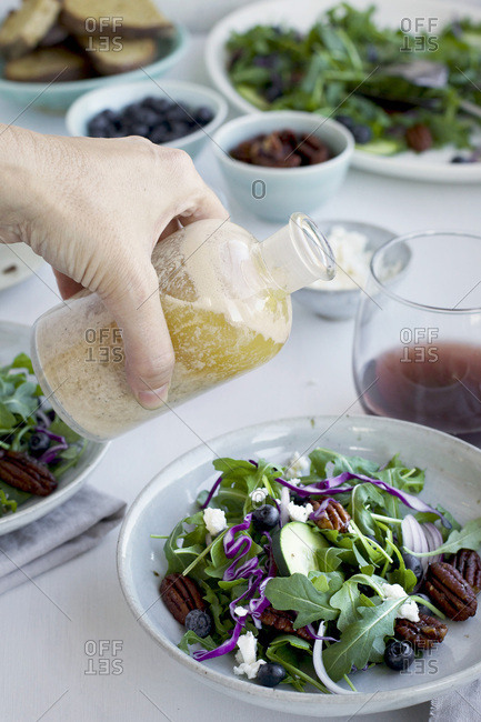 Hand pouring Toasted Walnut Sherry Feta Vinaigrette onto a Spicy Pecans Feta Arugula Salad served with bread and red wine