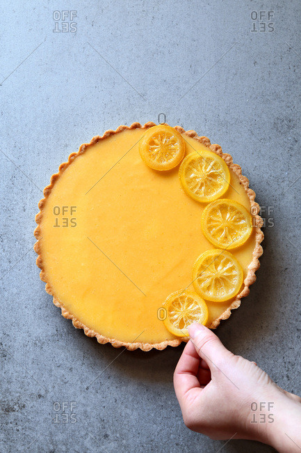 Female hand decorating a lemon tart with lemon slices