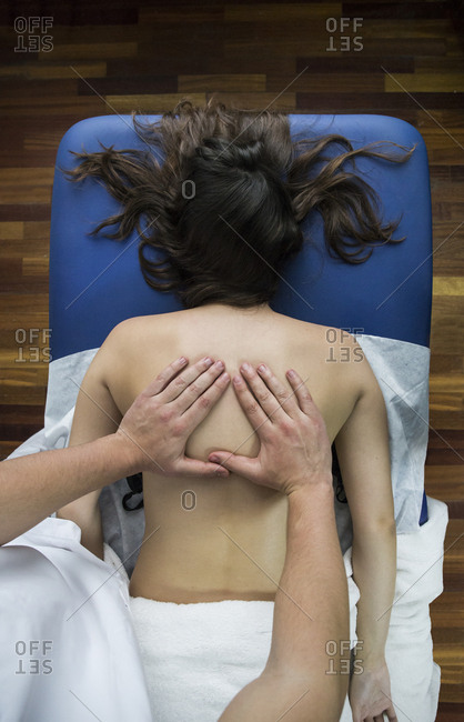 Hands of a physiotherapist massaging a client's back in a clinic