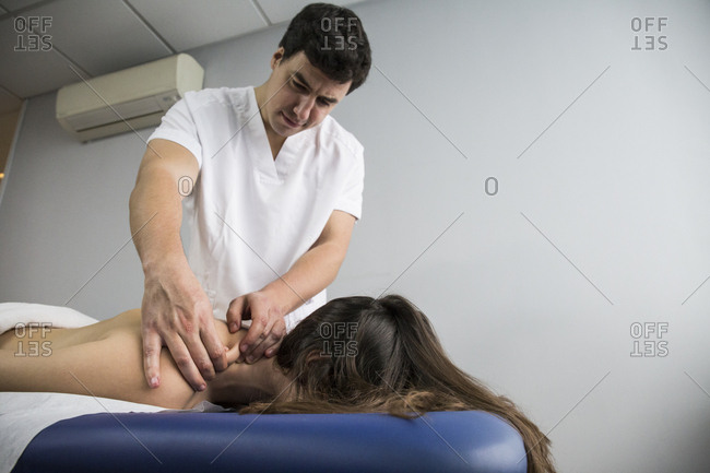 Physiotherapist massaging a client's neck in a clinic