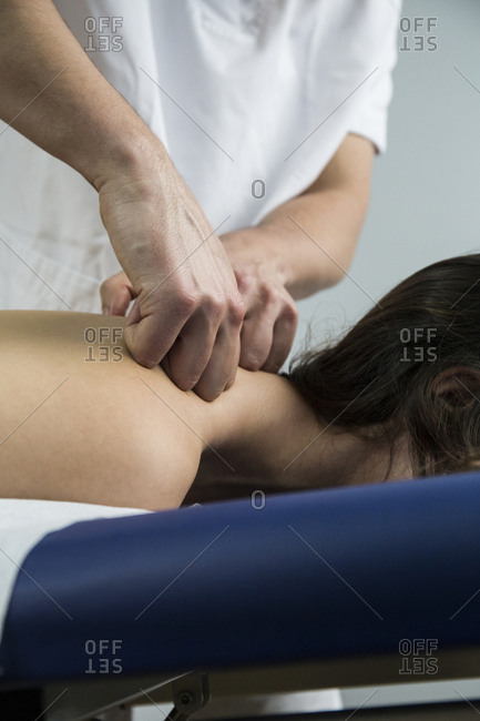Hands of a physiotherapist kneading a client's shoulder